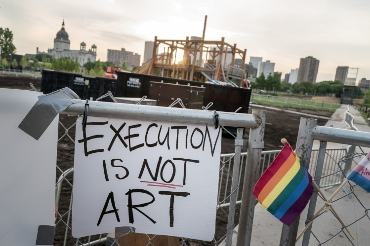 "A protest sign against Sam Durant's ""Scaffold"" sculpture on the perimeter fence of the Walker Art Center's sculpture garden / flickr - Lorie Shaull"