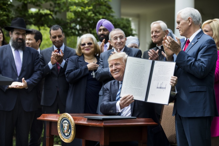 Donald Trump shows his signed Executive Order on Promoting Free Speech and Religious Liberty in May 2017 / CNS photo