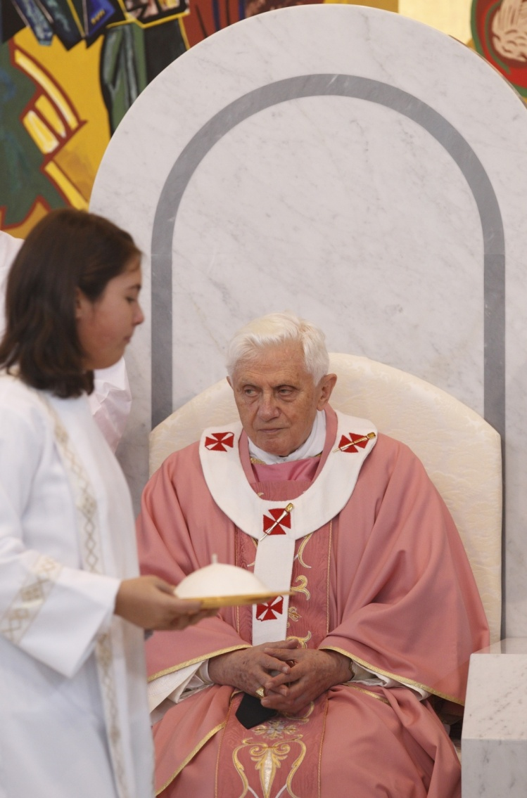 A girl altar server carries Pope Benedict XVI's zucchetto during his visit to St. Maximilian Kolbe Parish in Rome