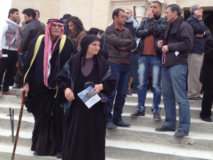 A Christian husband and wife, both wearing traditional Jordanian head  scarves, after a Mass