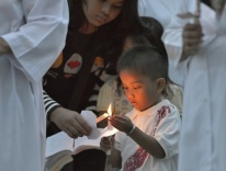 A boy helps light candles at Mass in Banda Aceh / CNS