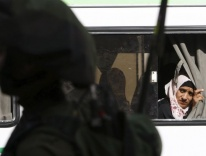 Palestinian woman looks out a bus window in Hebron, West Bank / CNS photo