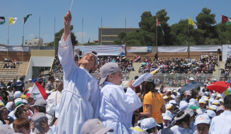 A First Communicant waves a Jordan flag at the Pope's Mass in Amman.